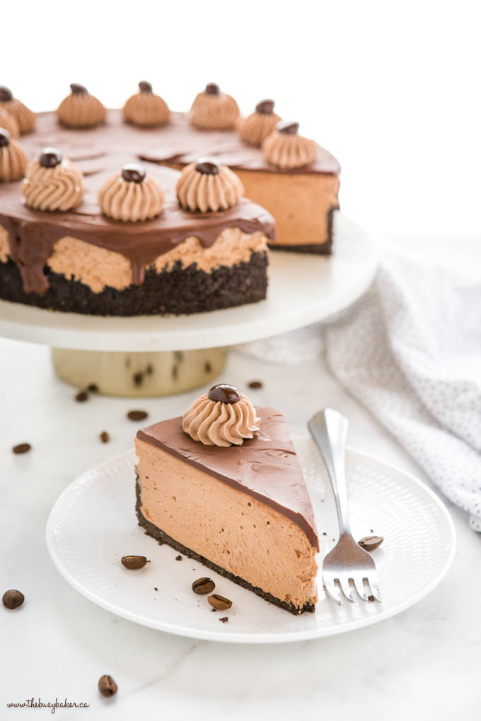 slice of coffee cheesecake on white plate with fork