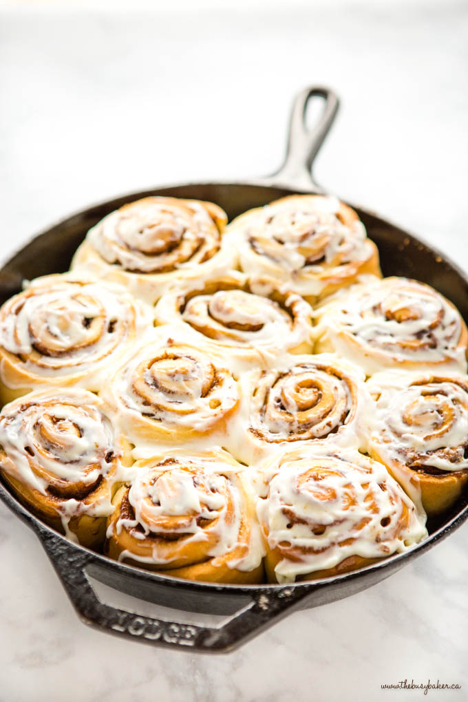 easy cinnamon rolls in a cast iron skillet with cream cheese frosting