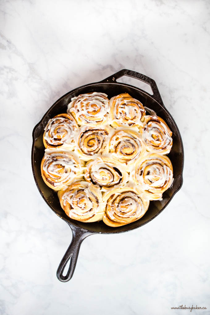 overhead image: cast iron skillet with cinnamon rolls and cream cheese frosting