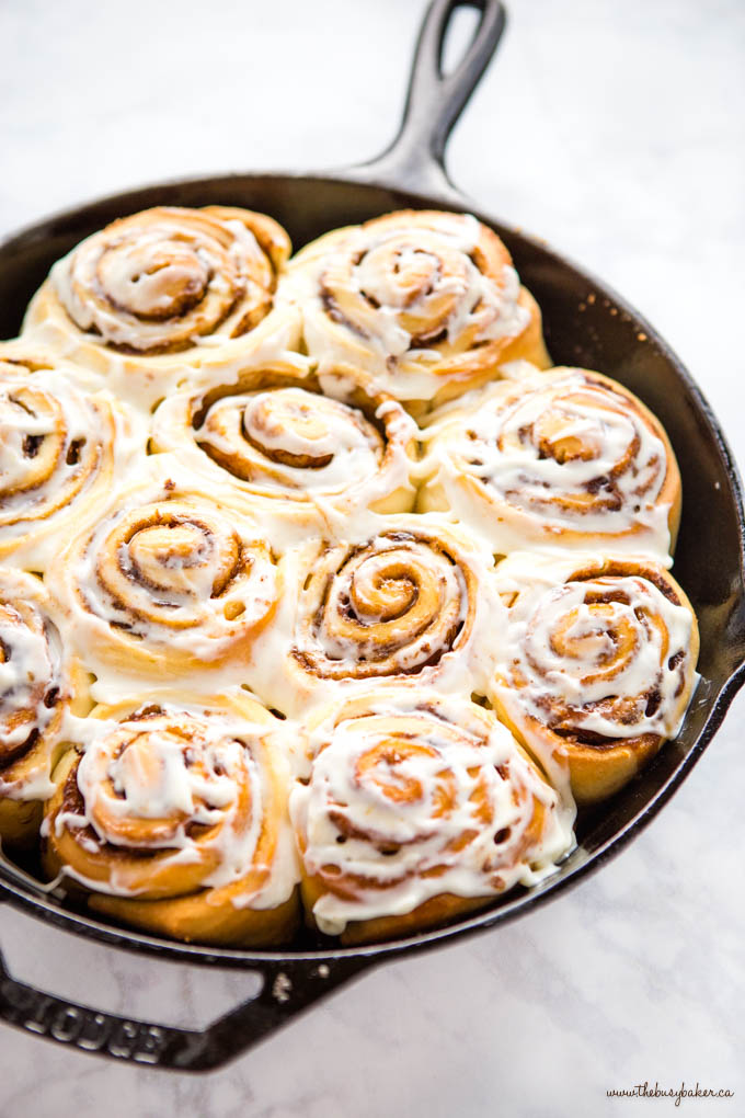 cast iron skillet with cinnamon rolls with cream cheese frosting
