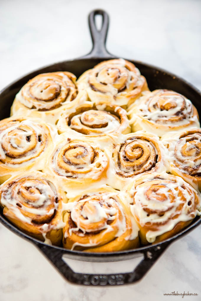 cast iron skillet with one-hour cinnamon rolls and cream cheese frosting
