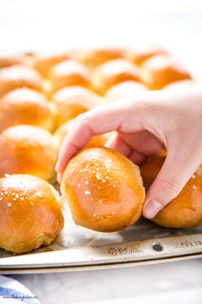 hand reaching for golden brown dinner roll with flaky sea salt on top