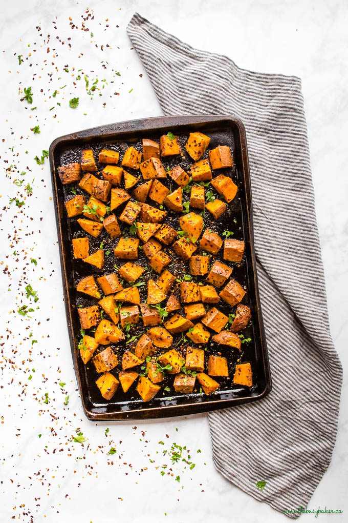 overhead image: back sheet pan with sweet potatoes, chili flakes, and honey