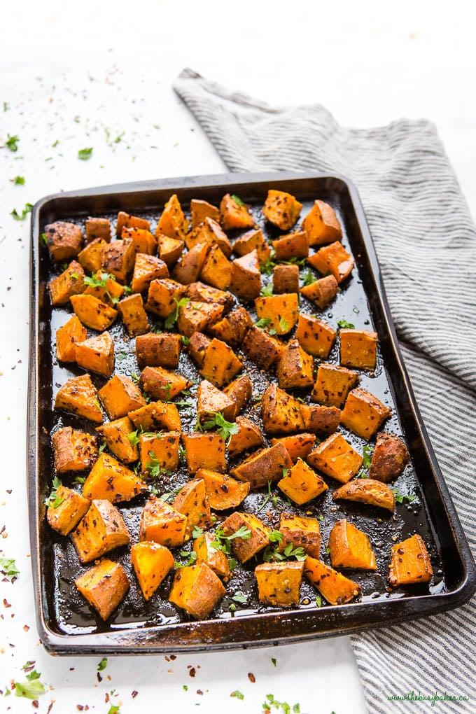 black sheet pan with baked sweet potatoes