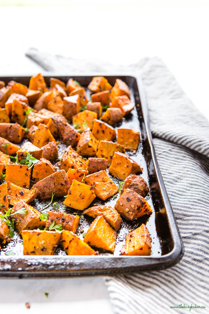 black sheet pan with spicy baked sweet potatoes