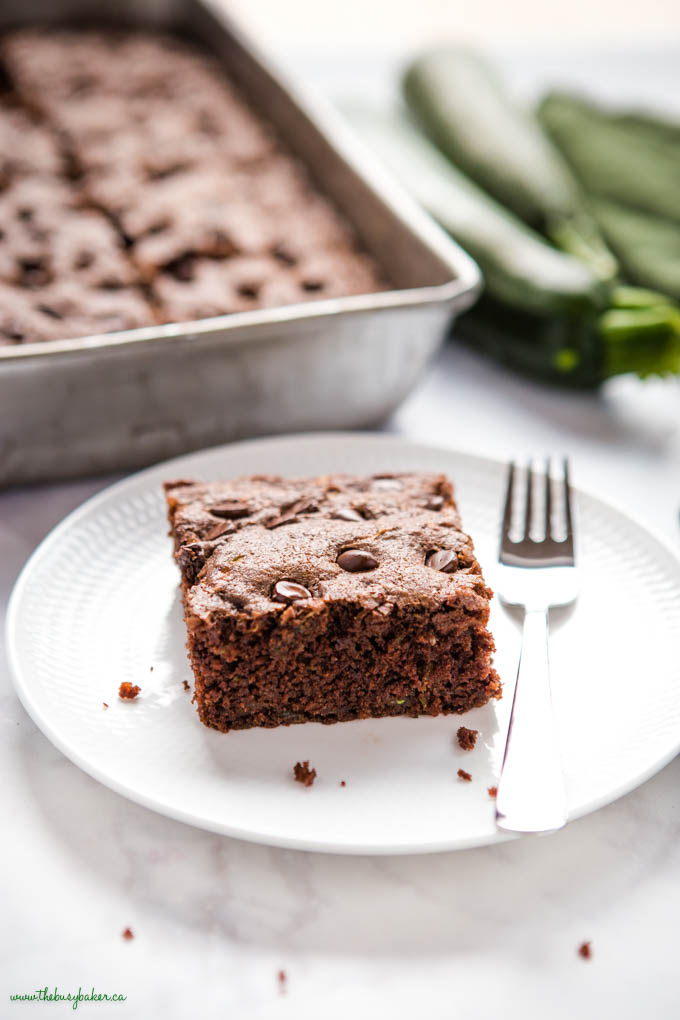 slice of moist zucchini chocolate cake on white plate with fork