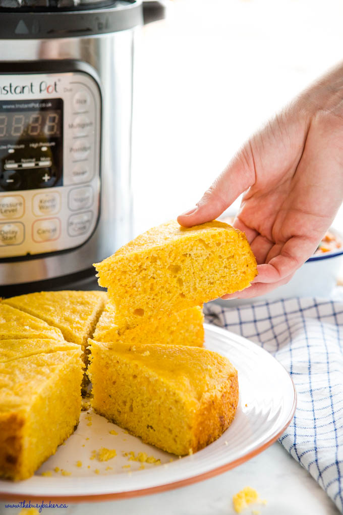 hand holding a slice of cornbread