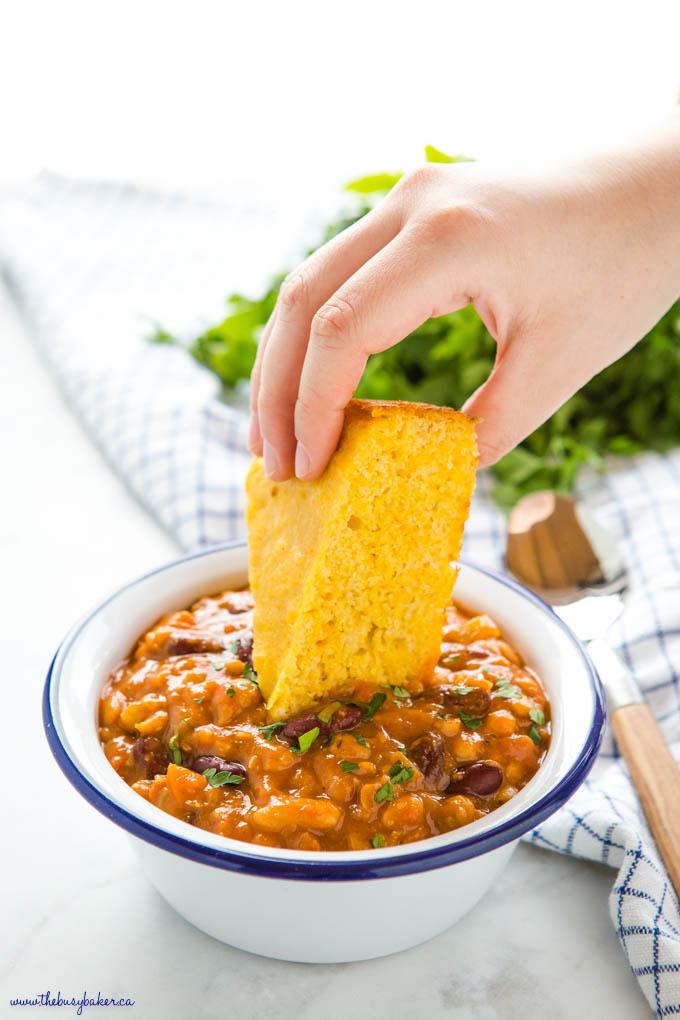hand dipping cornbread into vegan chili