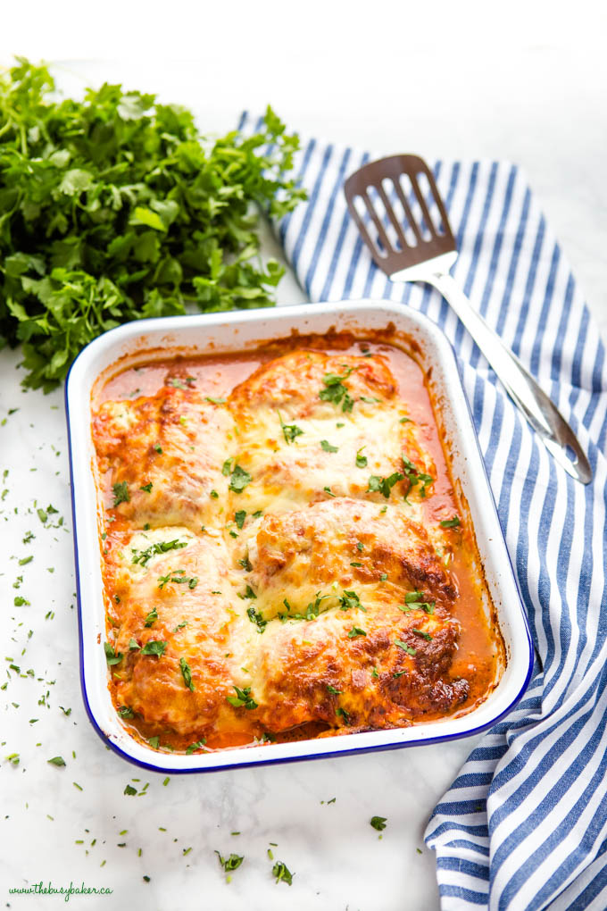 white pan with lasagna stuffed chicken topped with cheese