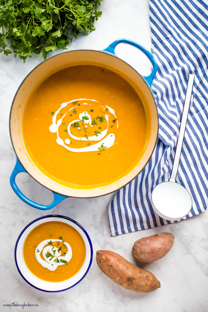 overhead image: sweet potato soup in blue cast iron pot with white ladle and herbs