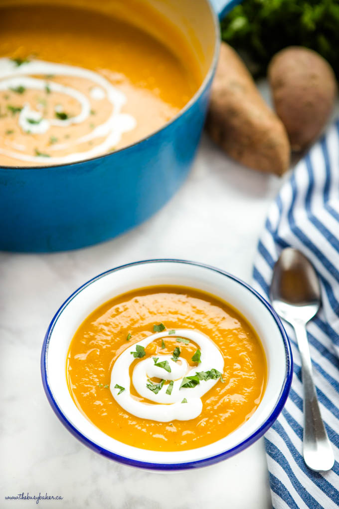 bowl of sweet potato soup with coconut cream and chopped herbs