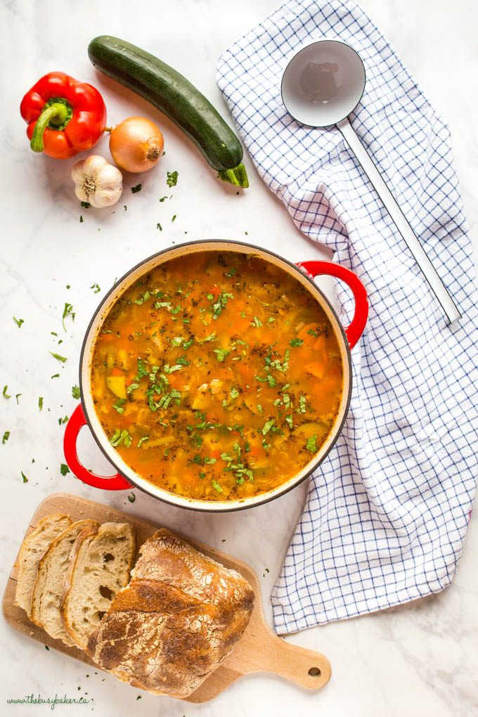 overhead image: vegetable soup with fresh herbs in red cast iron pot