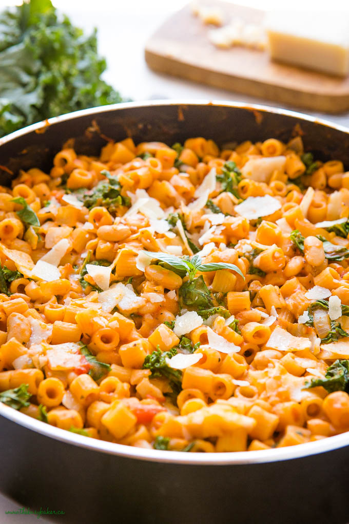 pasta with white beans in black pan with fresh basil