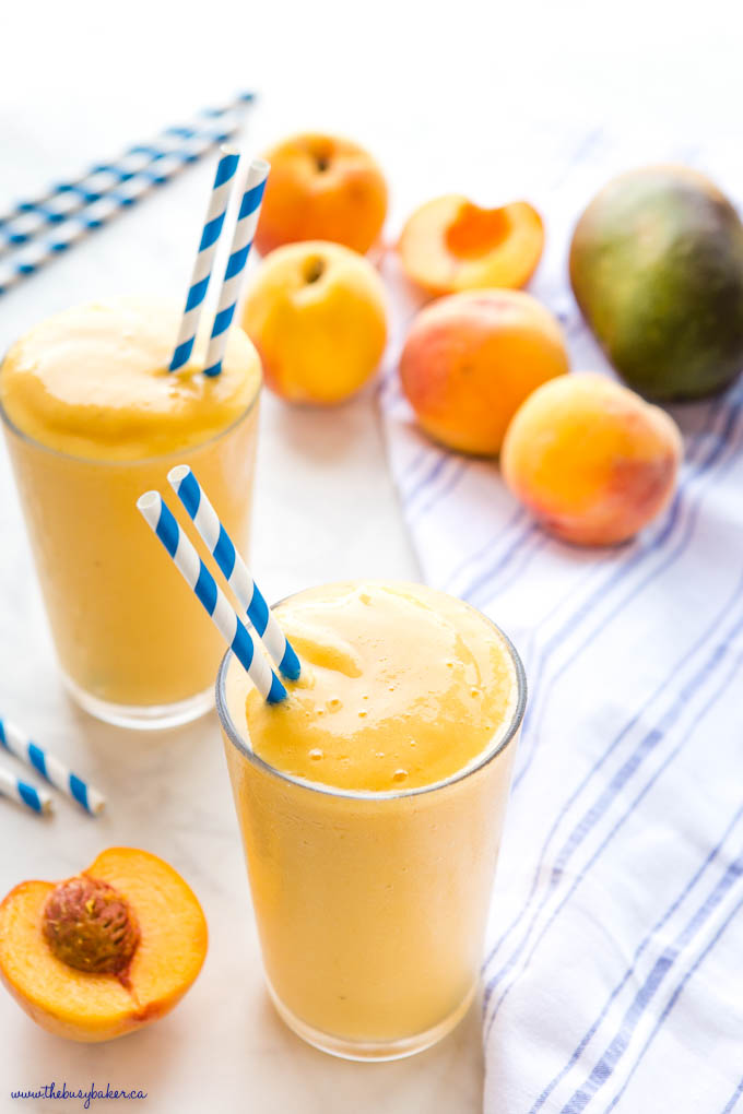 peach mango smoothie in glass with blue striped paper straws
