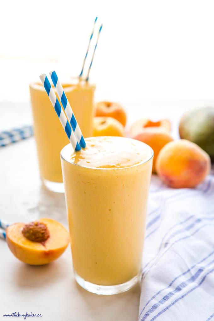 peach mango smoothie in tall glass with blue striped paper straws