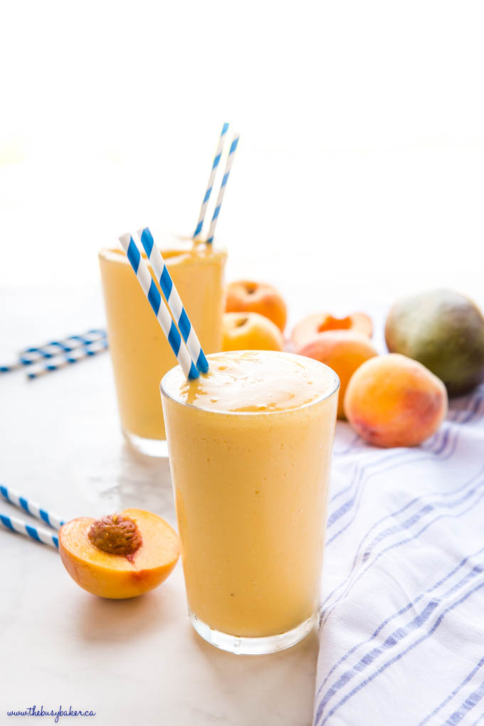 yellow peach mango smoothie in a large glass with blue straws