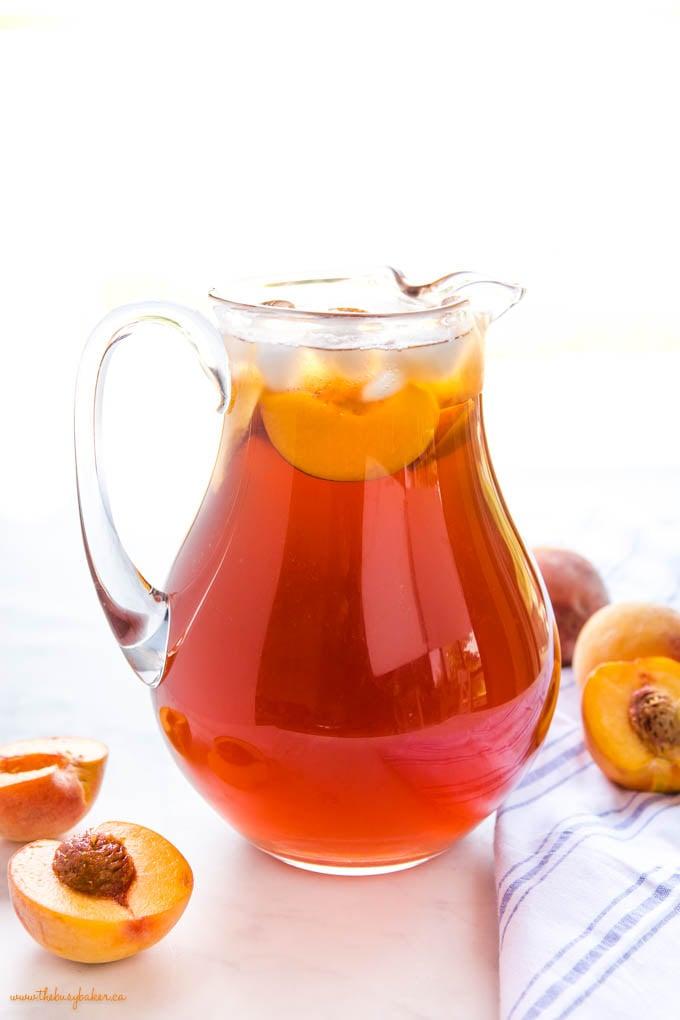 pitcher of peach tea with fresh peaches