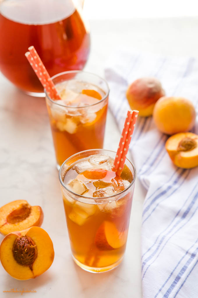 2 glasses of peach iced tea with ice and orange paper straws