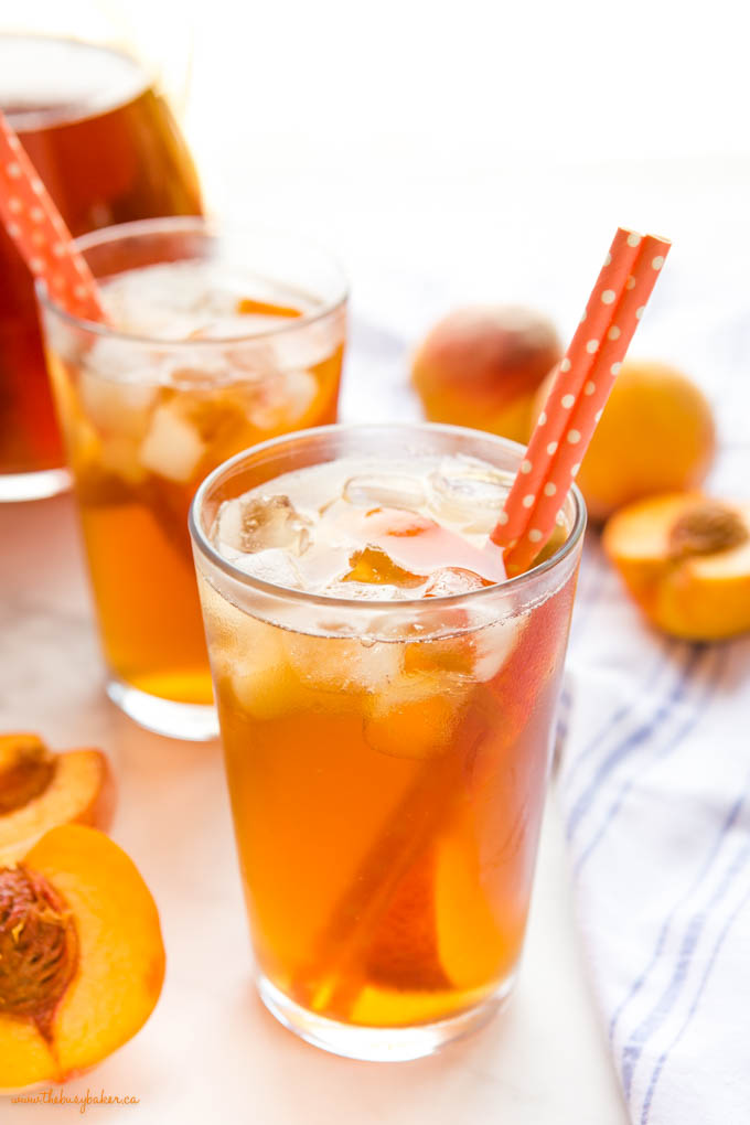 glass of fresh peach iced tea with ice and paper straws