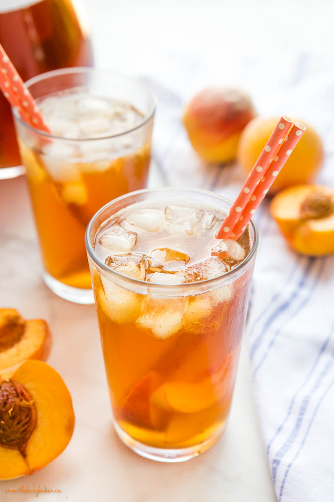 glass with peach iced tea and orange paper straws