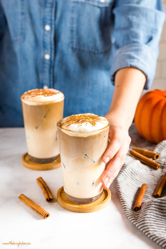 hand holding pumpkin spice iced latte