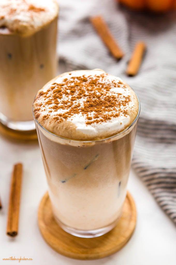 closeup image: pumpkin spice iced latte with foam