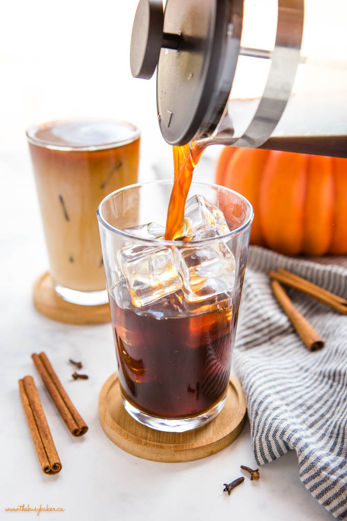 french press pouring cold brew coffee into a glass with ice