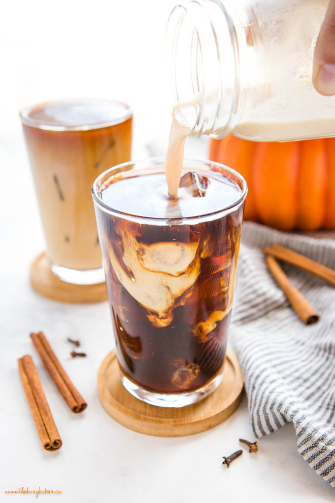 pouring pumpkin sweet cream over cold brew coffee in tall glass with ice