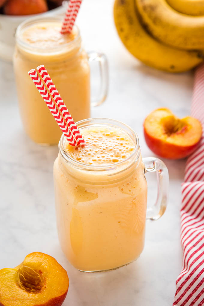 banana peach smoothie in glass with red chevron paper straws