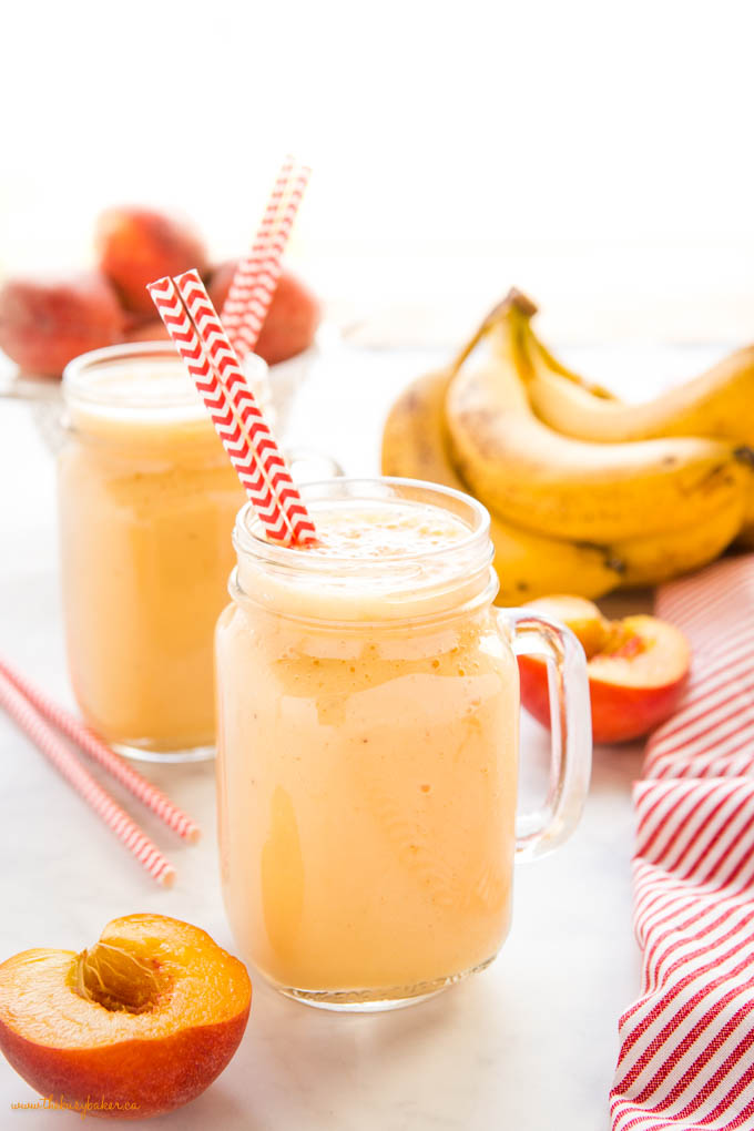 banana peach smoothie in glass with paper straws