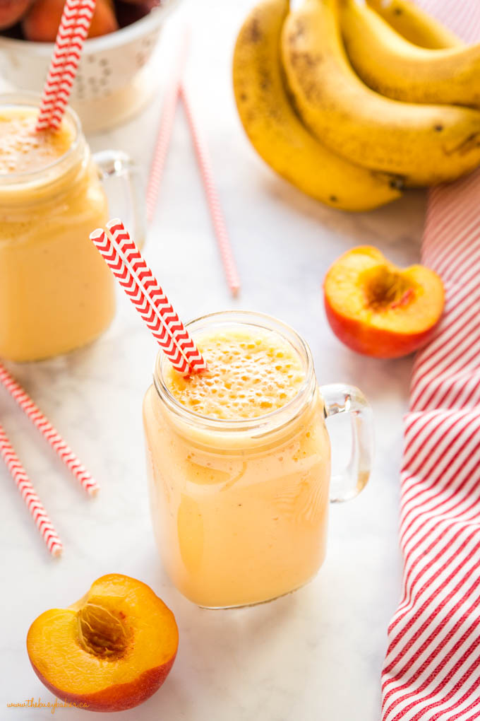 glass with banana peach smoothie and paper straws