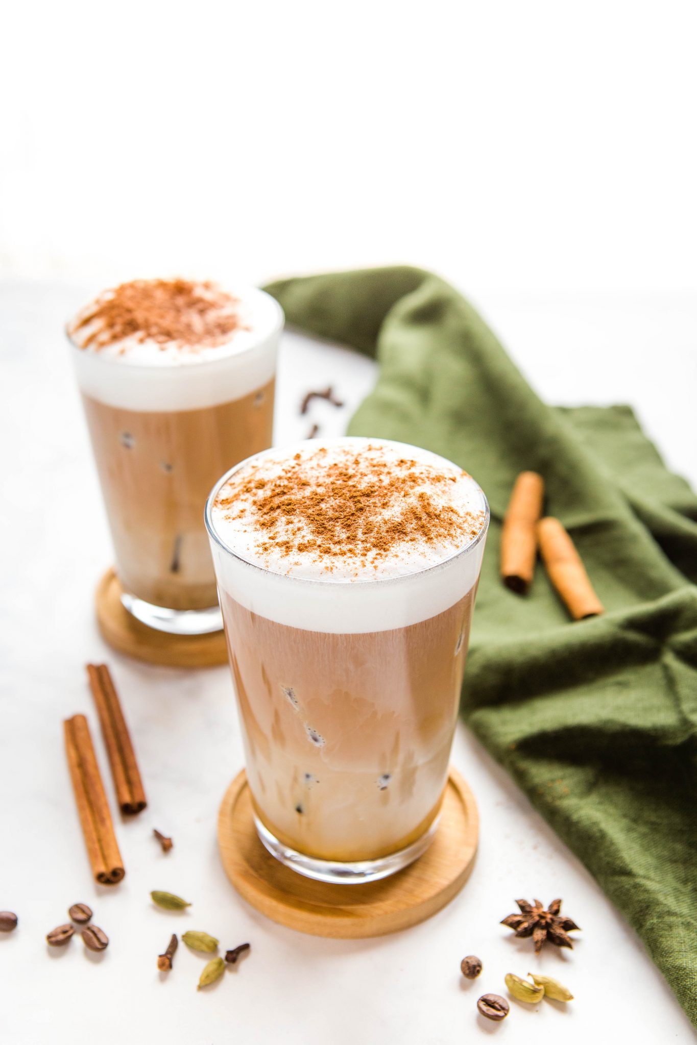 dirty chai latte in glass with foamed milk and cinnamon