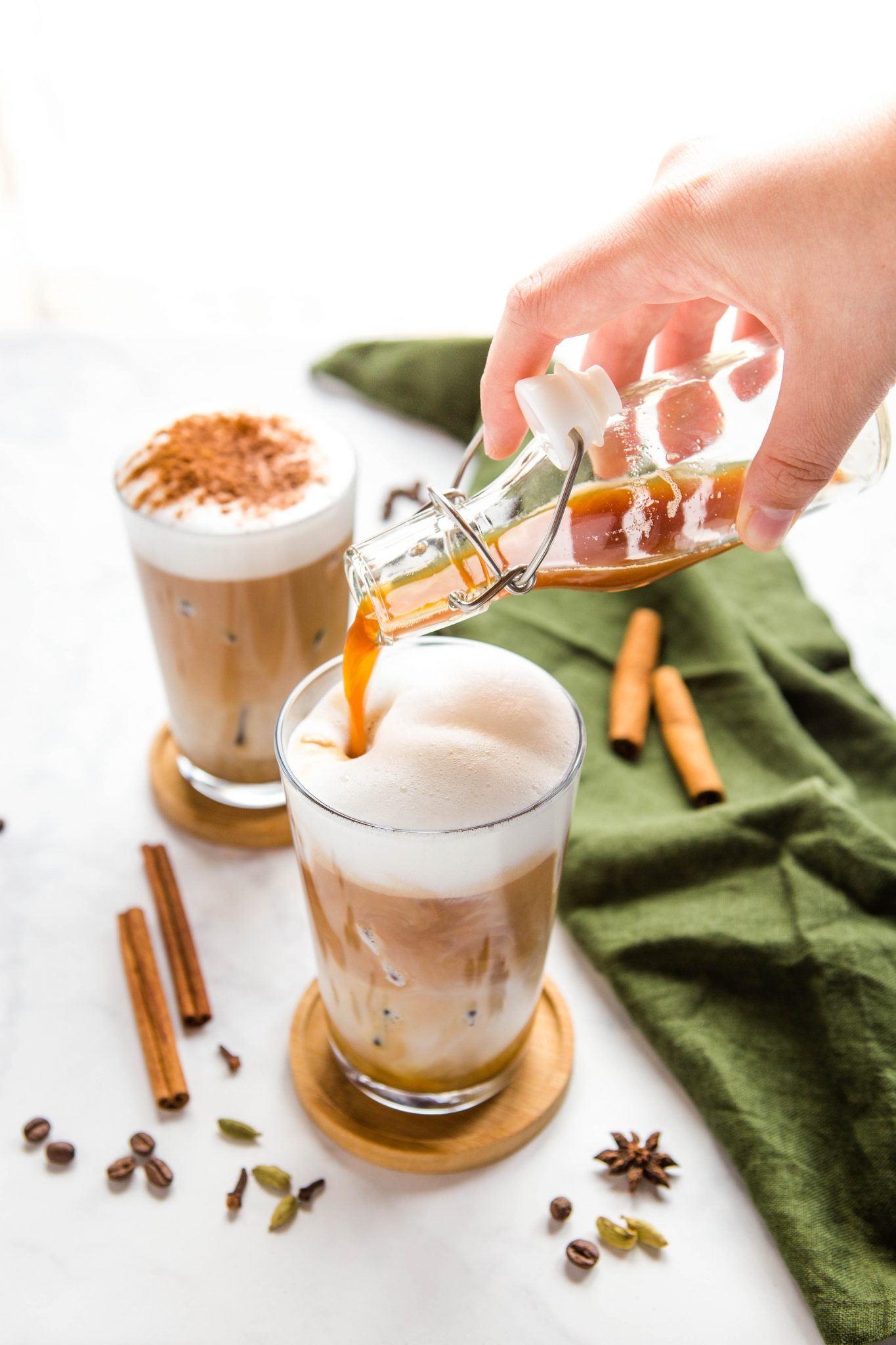 pouring chai tea into a glass over ice with espresso and foamed milk