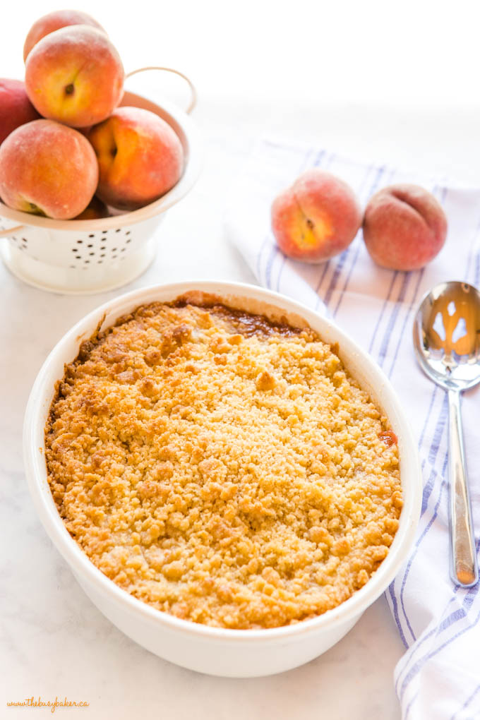 peach crumble with golden brown topping and fresh peaches