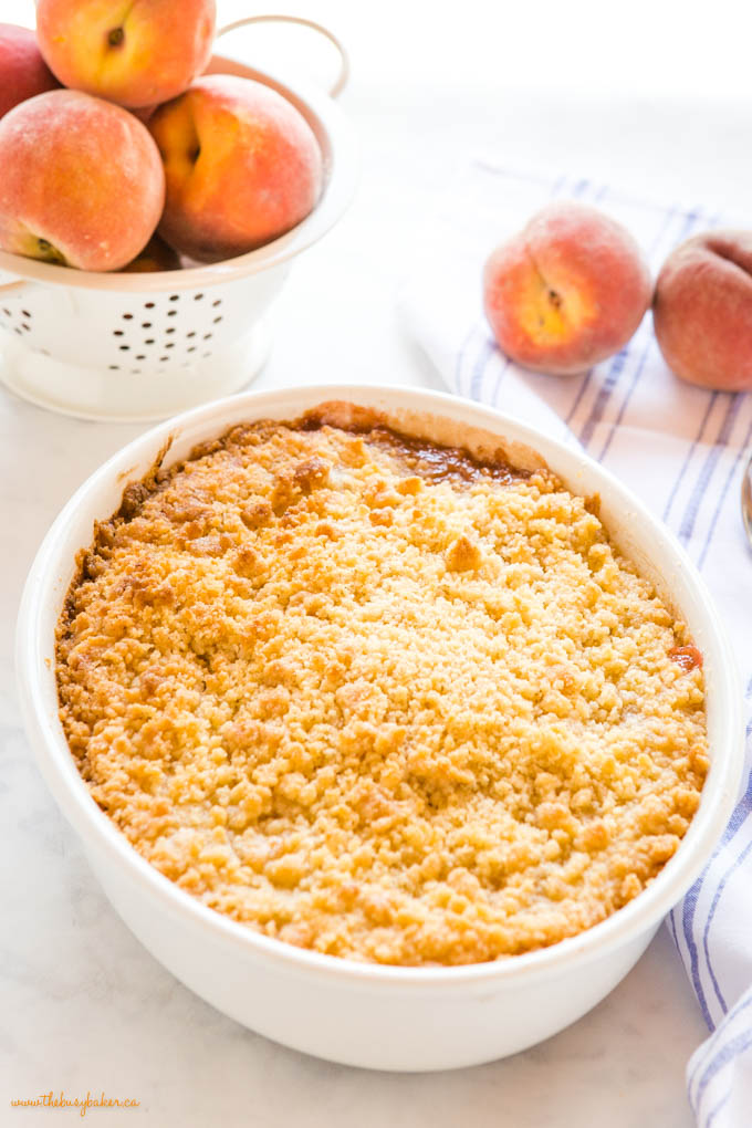 peach crumble in white oval baking dish with fresh peaches