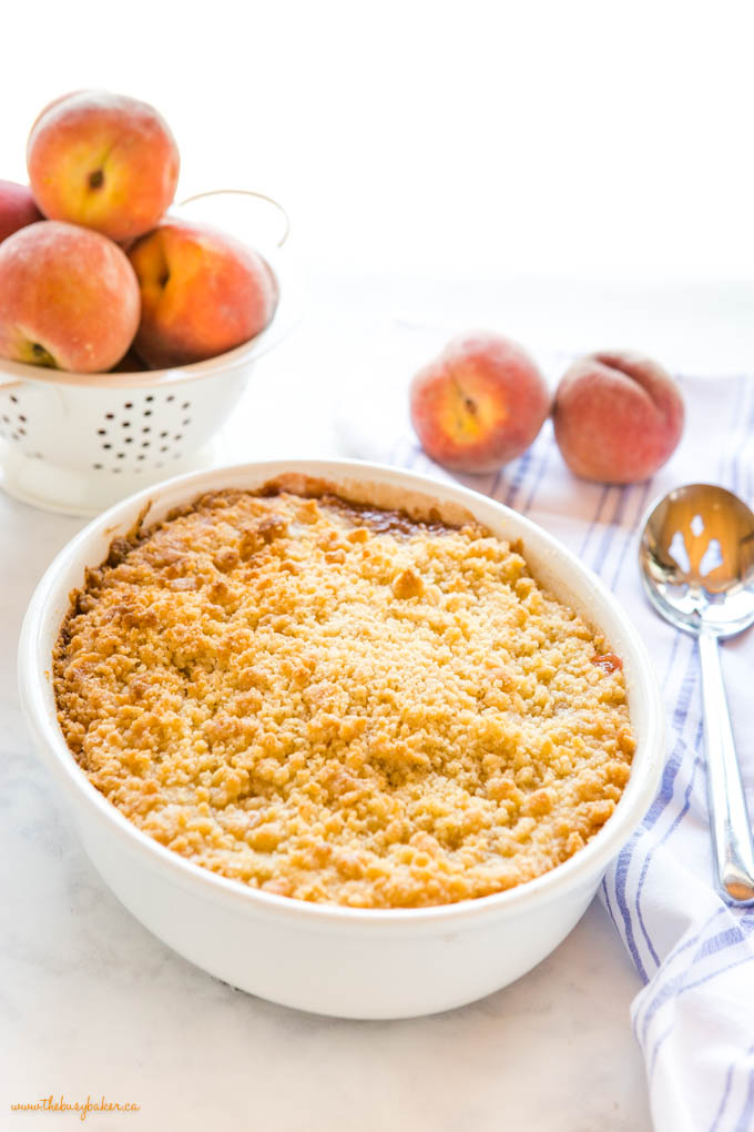 fresh peach crumble in white oval baking dish with serving spoon