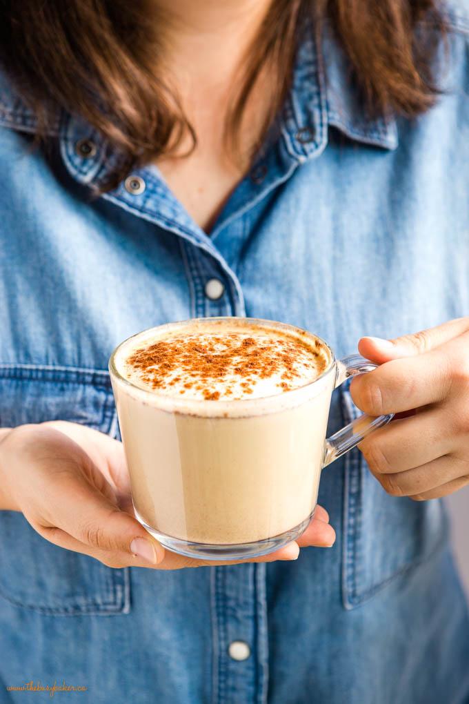 woman wearing denim shirt holding a pumpkin spice latte in a glass mug
