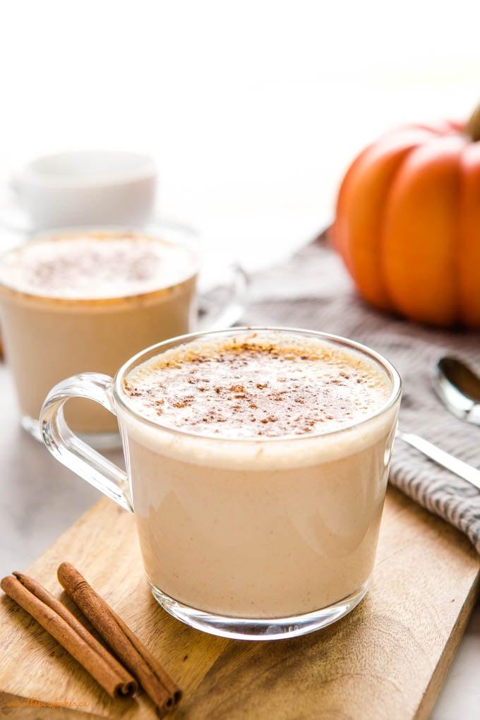 homemade pumpkin spice latte in glass mug with cinnamon sticks
