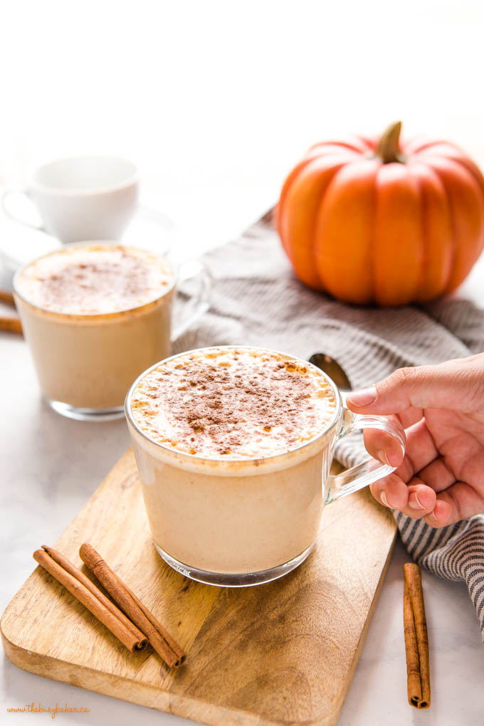 hand holding glass mug with homemade pumpkin spice latte