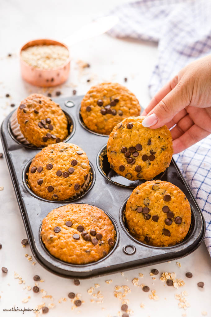 hand reaching for chocolate chip oatmeal muffins