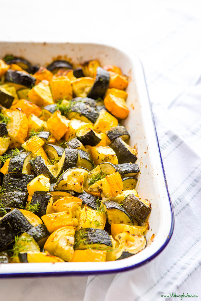 roasted zucchini and summer squash in white pan with blue rim